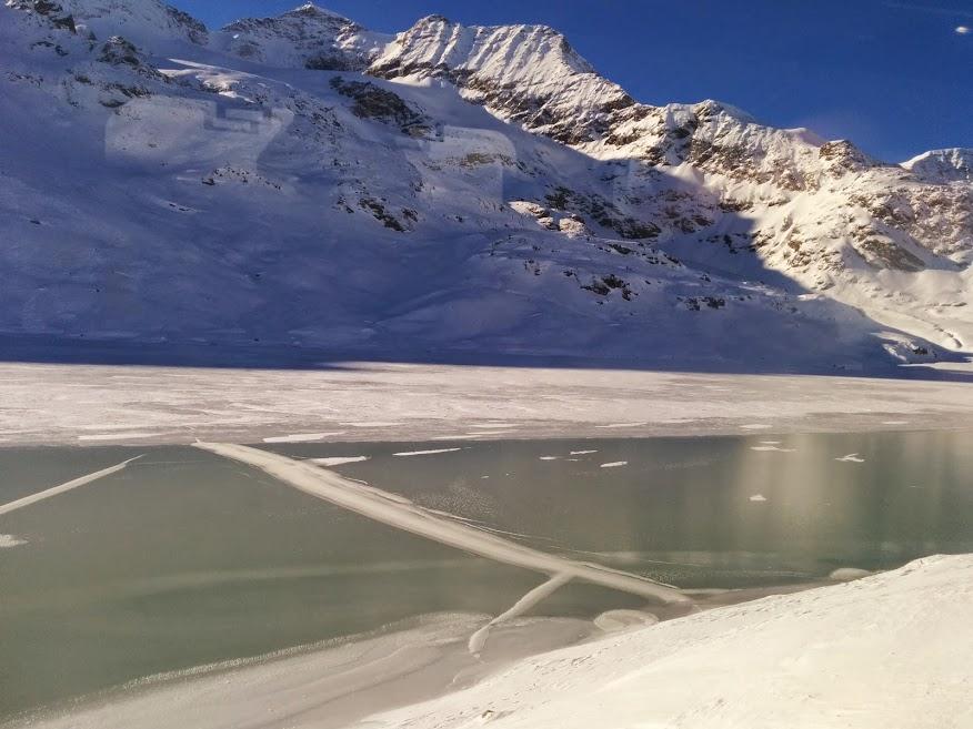 Montagne innevate, uno specchio d'acqua ghiacciato e il cielo blu.  Spettacolo naturale suggestivo che si apre davanti agli occhi di chi percorre il tragitto da Tirano a Saint-Moritz nel periodo invernale