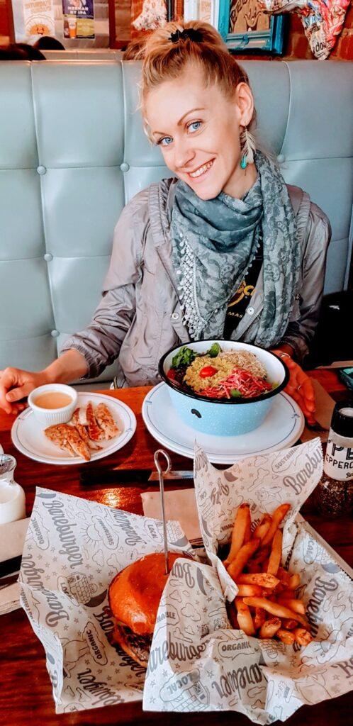 Pranzo vario a Brooklyn con insalata di quinoa, pollo speziato, hamburger accompagnato da patate fritte