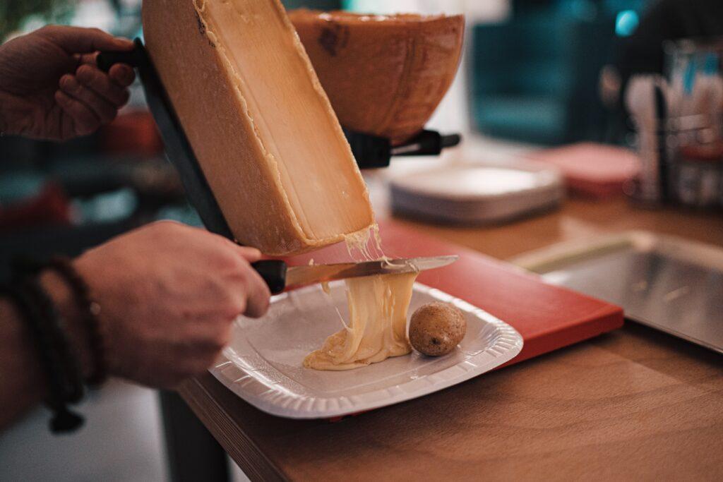 La tipica raclette calda e filante che si accompagna alle patate al cartoccio. Le migliori ricette del mondo svizzero.