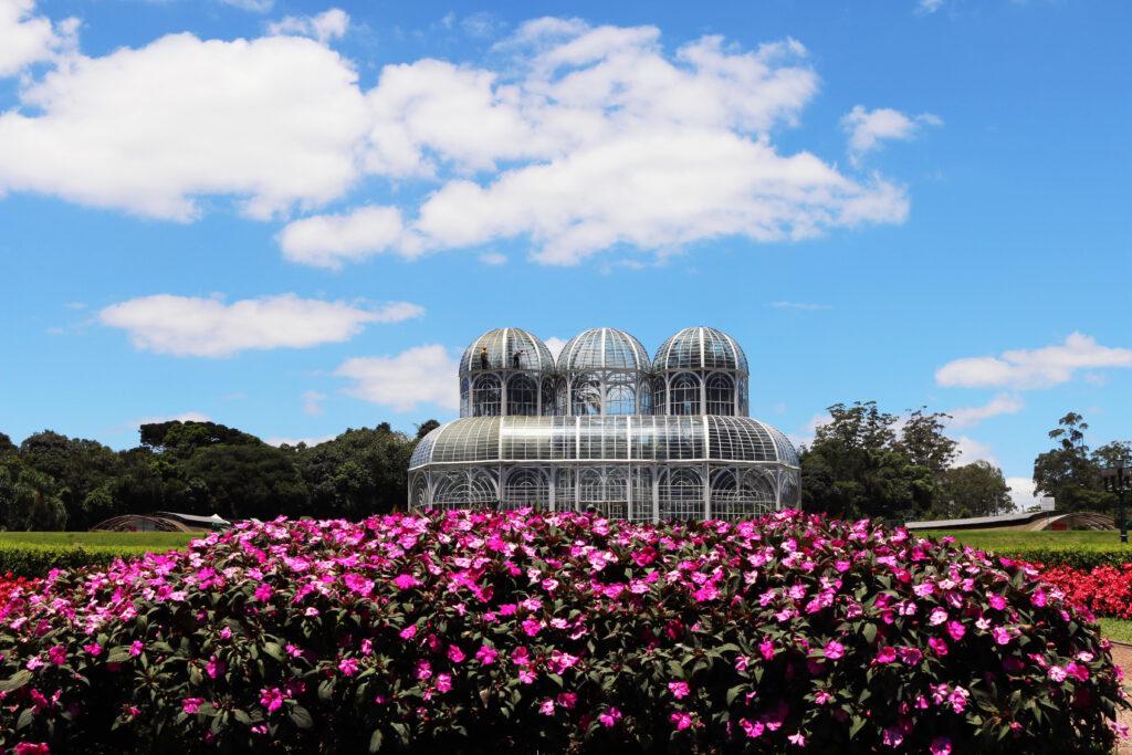 Il Giardino Botanico a Curitiba in Brasile circondato da prato verde e fiori in una giornata di sole.